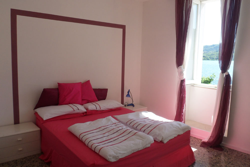 Newly refurbished bedroom area of apartment 'Isola', with superb view of Piazza Motta and the island of San Giulio
